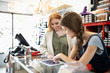 Female business owners using digital tablet at counter in art supply shop