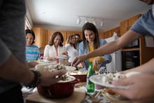 Latinx Family Enjoying Buffet Dinner In Kitchen