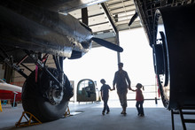 Female Army Engineer Mother Walking With Children In Military Airplane Hangar