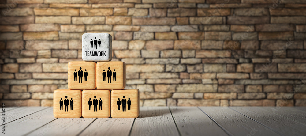 Fototapeta cubes with the word TEAMWORK and person-symbols stacked as a pyramid in front of a brick wall