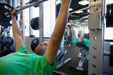 Focused Man Exercising, Doing Chest Press With Barbell In Gym