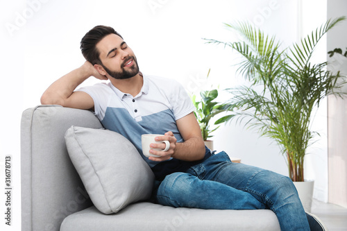 Photo Young man with cup of drink relaxing on couch at home