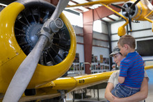 Female Army Pilot Mother Showing Son Airplane In Military Airplane Museum