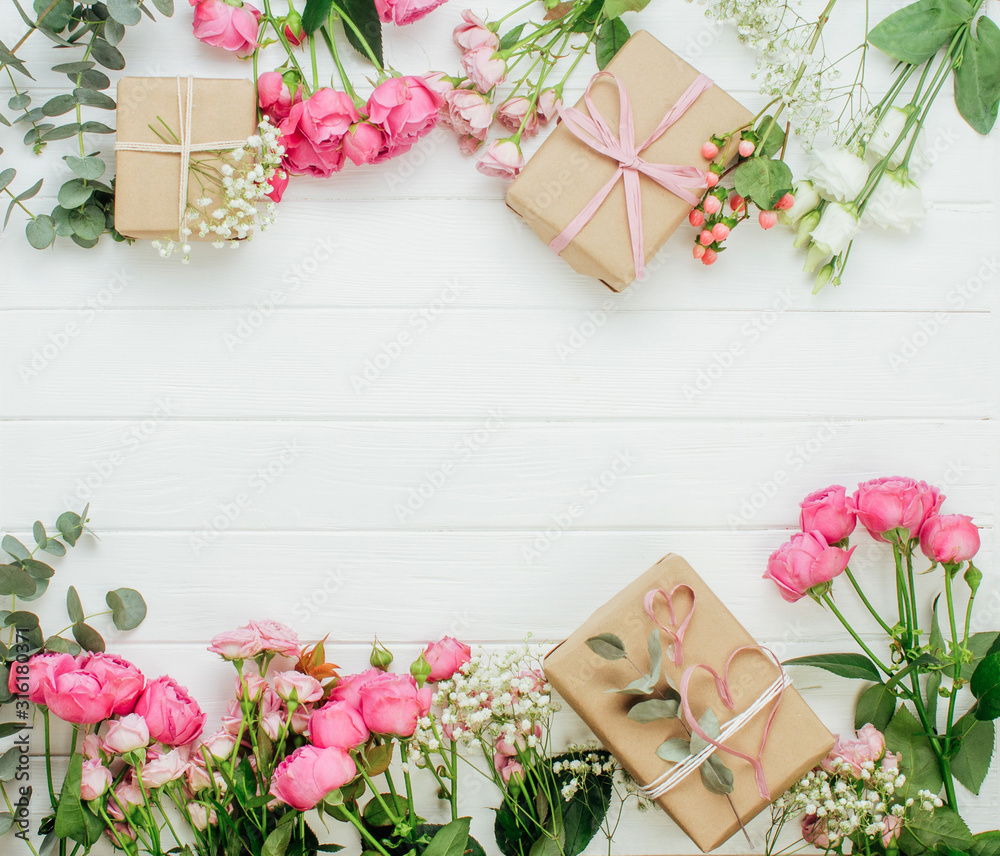 Fototapeta Craft paper wrapping gift boxes and flowers on white wooden background