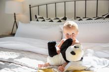 Portrait Cute Baby Girl Holding Stuffed Panda On Bed