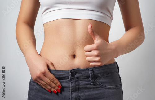 Obraz slim, athletic waist of a young woman on white background. - fototapety do salonu