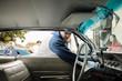Latinx man reaching inside vintage car
