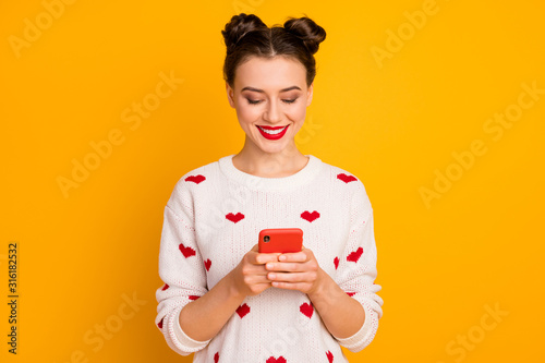 Portrait of her she nice-looking glamorous attractive lovely pretty charming cute cheerful girl using device chatting with boyfriend isolated over bright vivid shine vibrant yellow color background