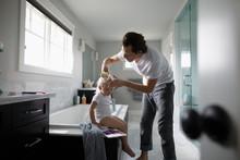 Father Brushing Toddler Daught...