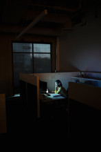 Dedicated Businesswoman Working Late At Computer In Dark Office Cubicle
