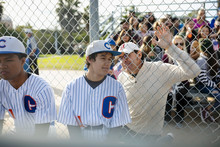 Latinx Father Talking To Baseball Player Son At Fence