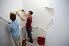 Father And Son Using Tape Measure, Measuring Wall Above Stairs