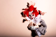 Scary Clown Killer Breaks Through The Wall. Horror. Halloween Concept.