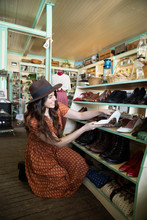 Smiling Woman Shopping, Looking At Shoes In Vintage Shop