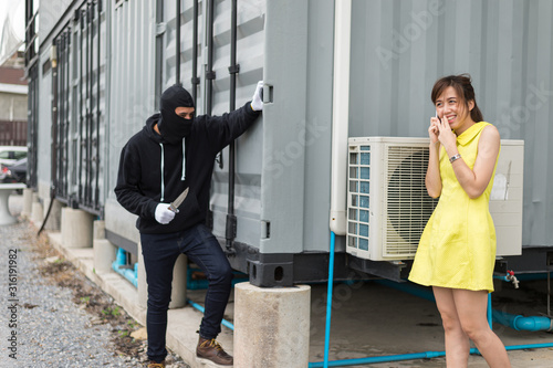 Fotografia woman walk and talking with friend by smartphone while bandit wear black mask and black clothes holding knife are dodging the corner of the building