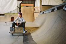 Teenage Boy With Skateboard Si...