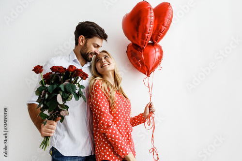 Obraz Couple. Love. Valentine's day. Emotions. Man is giving heart-shaped balloons to his woman, both smiling; on a white background - fototapety do salonu