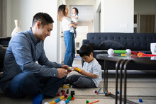 Father And Son Playing With Plastic Blocks In Living Room