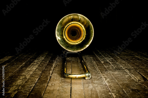 yellow brass instrument trombone lies on the wooden floor of the stage Canvas Print