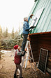 Couple installing solar panels on cabin roof