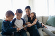 Happy mother and children using digital tablet on living room sofa