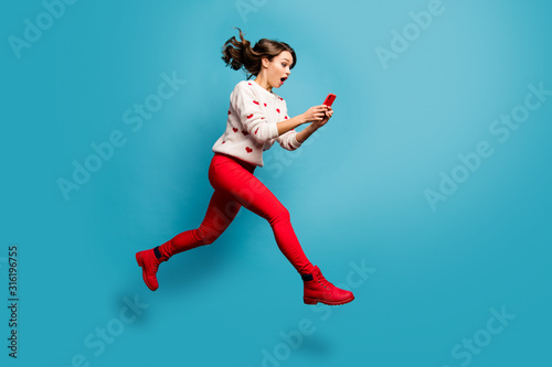 Fototapeta Full length body size view of nice attractive cheerful amazed impressed girl jumping using 5g like follow subscribe running hurry rush isolated on bright vivid shine vibrant blue color background obraz