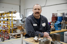 Portrait Confident Male Machinist Working In Factory