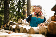 Man Stacking Firewood Outside Cabin