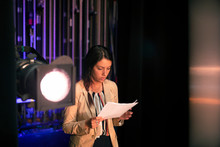 Female Speaker Reviewing Notes Backstage