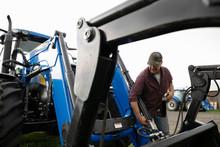 Male Farmer Fixing Tractor