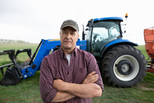 Portrait Confident Male Farmer Standing In Front Of Tractor