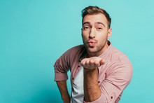 Smiling Handsome Man Blowing Air Kiss Isolated On Blue