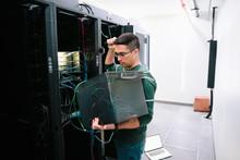 Male IT Technician Examining E...