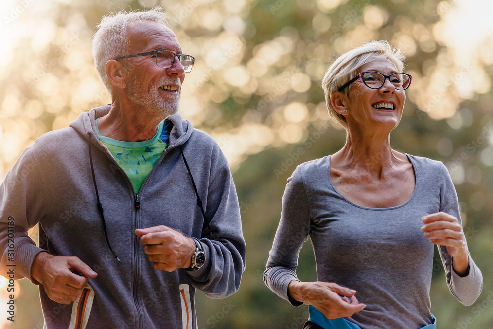 Fototapeta Cheerful active senior couple jogging in the park. Exercise together to stop aging.