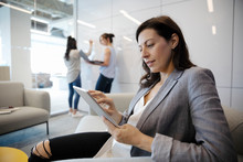 Businesswoman Using Digital Tablet In Conference Room Meeting