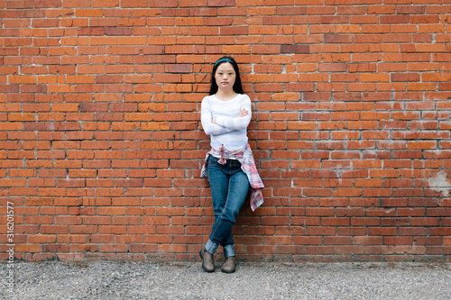 Portrait confident young woman with down syndrome leaning against brick wall - 316201577