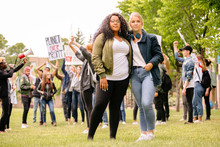 Portrait Of Students Standing On Grass At Environmental March