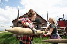 Female Farmers Unloading Wooden Fence Posts On Farm