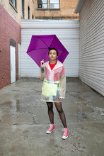 Portrait Confident Young Woman With Purple Umbrella Wearing Rain Poncho In Urban Alley