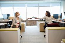 Businesswomen Exchanging Paper...