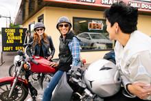 Happy Women Friends On Motorcycles In Parking Lot Of Drive-in