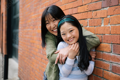 Portrait happy mother and daughter with down syndrome hugging at brick wall - 316203986