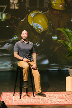 Portrait Confident Male Firefighter With Tattoos Giving Inspirational Speech On Stage
