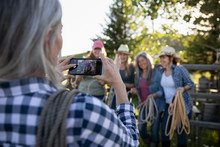 Woman Photographing Friends At Roping Class On Ranch