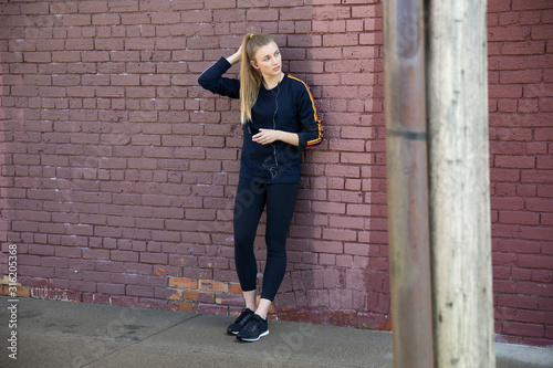 Young female runner resting against brick wall - 316205368