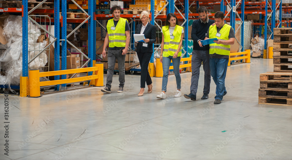 Fototapeta Warehouse staff meeting, workers with mnagers