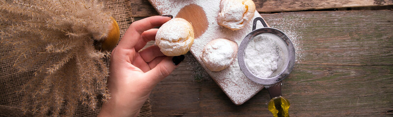 Banner with woman hand decorating with icing sugar some profiteroles.