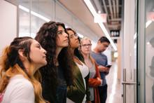 Students Looking At Notice Board In University Corridor