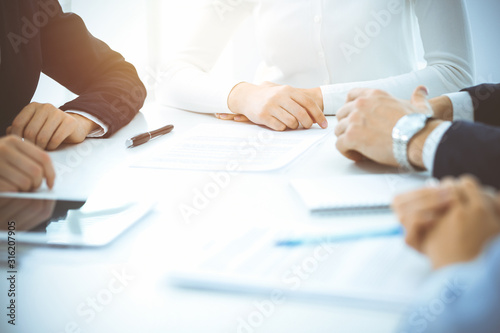 Obraz Group of unknown business people and lawyers discussing contract in sunny office. Teamwork and meeting concepts - fototapety do salonu