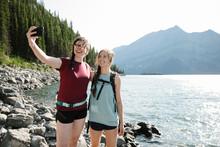 Happy Female Hiker Friends Taking Selfie At Sunny Lakeside